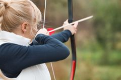 Attractive woman practicing archery. Outdoors Royalty Free Stock Image