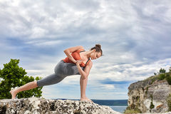 Attractive woman is practicing yoga on the rock against beautiful landscape. Stock Photos