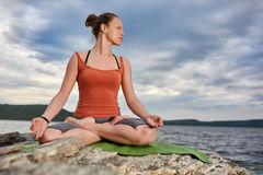 Attractive woman is practicing yoga on the stone near beautiful river. Stock Photography