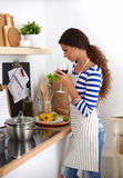 Attractive woman preparing food in the kitchen Stock Photos
