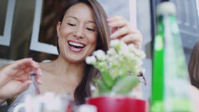 Attractive woman preparing a hot drink at a cafe whilst talking happily stock video