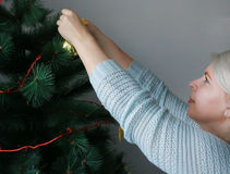 Attractive woman preparing the tree for Christmas Royalty Free Stock Image