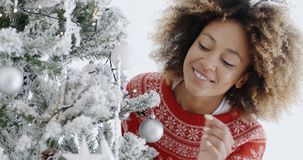 Attractive woman preparing the tree for Christmas. Attractive young African woman with a wild afro hairstyle preparing the tree for Christmas hanging decorations stock video footage