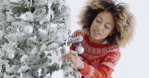 Attractive woman preparing the tree for Christmas. Attractive young African woman with a wild afro hairstyle preparing the tree for Christmas hanging decorations stock video