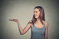 Attractive woman presenting copy space isolated on gray wall background Stock Photography