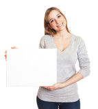 Attractive woman presents a blank board. Young woman with long hair presents a blank sign for advertising on an isolated white background Royalty Free Stock Photo