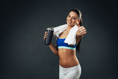 Attractive woman with a protein shake holding thumbs up Royalty Free Stock Photos