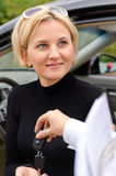 Attractive woman purchasing a car. Being handed the ignition keys by the saleslady on completion of the deal Stock Images