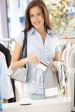 Attractive woman purchasing shirt. In clothes store with credit card, smiling at camera Royalty Free Stock Image