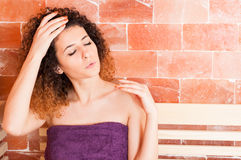 Attractive woman in purple towel warming in salt sauna Royalty Free Stock Image