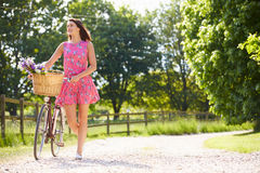 Attractive Woman Pushing Bike Along Country Lane Royalty Free Stock Photo