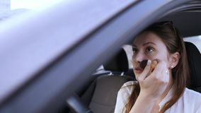 An attractive woman puts a blush with a large brush while sitting behind the wheel of a car. Early morning, a