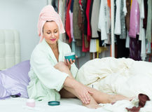 Attractive woman putting cream on legs Royalty Free Stock Photography