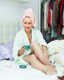Attractive woman putting cream on legs Royalty Free Stock Image