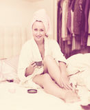 Attractive woman putting cream on legs Royalty Free Stock Photos