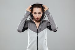 Attractive woman putting on her hood and looking at camera. Attractive fitness woman in earphones putting on her hood and looking at camera while standing  over Stock Photos