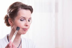 Attractive woman is putting her make up on Stock Photography