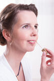 Attractive woman is putting her make up on Royalty Free Stock Photos