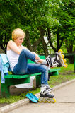 Attractive woman putting on roller blades. Attractive blond woman sitting on a park bench putting on roller blades as she prepares for a fun day skating Royalty Free Stock Photography