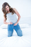 Attractive woman putting on tight jeans on a bed Stock Photography