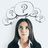 Attractive woman with question marks. Portrait of attractive thoughtful young businesswoman with drawn question marks. Confusion and challenge concept royalty free stock photos