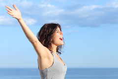 Attractive woman with raised arms shouting to the wind. In the beach with the sea and blue sky in the background Stock Images