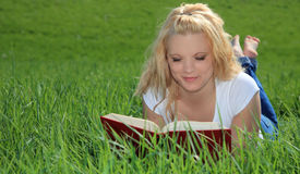 Attractive woman reading book outside Royalty Free Stock Image