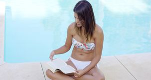 Attractive woman reading a book poolside stock video footage