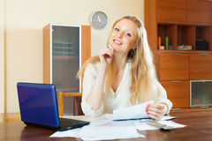 Attractive woman reading  document at home Royalty Free Stock Photos