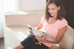 Attractive woman reading magazine Stock Images
