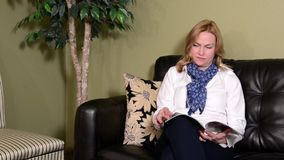Attractive woman reading a magazine in a waiting room stock video