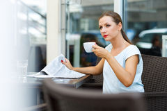 Attractive woman reading a newspaper and drinking morning coffee Stock Images