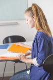 Attractive woman reading portfolio in office Stock Photos