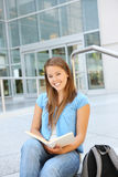 Attractive Woman Reading at School Library. Attractive young woman at school library holding book reading Royalty Free Stock Image