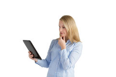 Attractive woman reading a tablet. Attractive woman with her hand on her chin reading a handheld touchscreen tablet Stock Photography