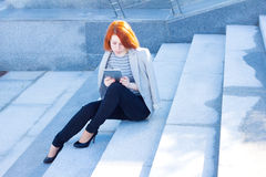Attractive woman reading a tablet and sitting outdoors Royalty Free Stock Photos