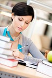 Attractive woman reads at the library. Woman with green apple surrounded with piles of books reads sitting at the table at the library. Academic achievement Stock Photography