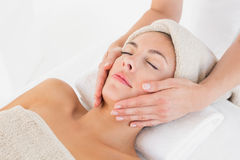 Attractive woman receiving facial massage at spa center Stock Image