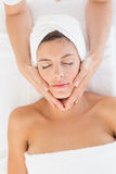 Attractive woman receiving facial massage at spa center Stock Photo