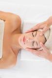 Attractive woman receiving facial massage at spa center Stock Photos