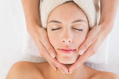 Attractive woman receiving facial massage at spa center Stock Photography
