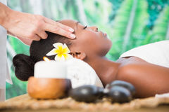 Attractive woman receiving temple massage at spa center Stock Photo