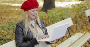 Woman using video chat app in park. Attractive woman in red beret sitting on bench and using video chat app on her laptop during walk in autumn park stock footage
