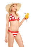Attractive woman in a red bikini holding a cocktail Royalty Free Stock Images