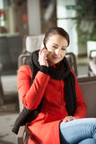 Attractive woman in red coat having a call Stock Photography