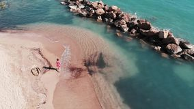 Attractive woman in red dress on beach. Young girl walking along beach. Aerial view of beautiful sandy beach with blue clear water stock video footage