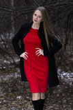Attractive woman in red dress and black coat standing in winter park Royalty Free Stock Photo