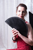 Attractive woman in red dress hiding behind fan Royalty Free Stock Image