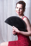 Attractive woman in red dress hiding behind fan Royalty Free Stock Photos