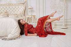 Attractive woman in a red dress lies near bed in bright interior Royalty Free Stock Photo